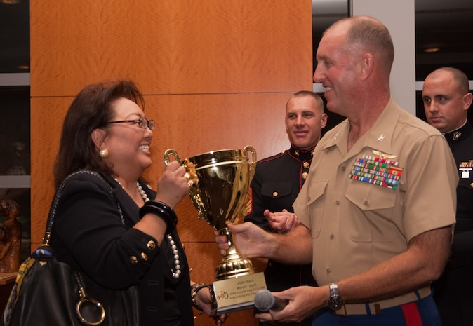 Colonel Robert Rice, Commander, Marine Corps Base Hawaii, presents Merrill Lynch Vice President Diane Kimura with the first place Tricycle Cup Competition trophy during a Toys for Tots corporate sponsors' reception Nov. 19. Merrill Lynch employees donated the most toys among downtown businesses during the Tricycle Cup toy collection competition which was held Nov. 17.