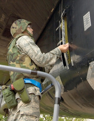 During an exercise, 1st Lt. Andrew Sturgeon measures a simulated battle-damaged B-52 to calculate the stress load of the area so he can design a repair for the expeditionary repair technicians. Lieutenant Sturgeon normally works in the Engineering Directorate, but is an aircraft battle damage repair-deployable engineer. The design is a recipe for repair, telling mechanics what materials are needed, including bolt patterns, patches and metals to use. (Air Force photo by Margo Wright)