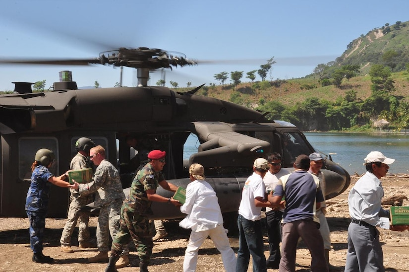 ILOPANGO, El Salvador - U.S. servicemembers, a Civil Affairs team, Salvadoran military and villagers from El Sauce help unload a UH-60 Blackhawk helicopter, assigned to Joint Task Force-Bravo, Nov. 17 near El Sauce, El Salvador. A Civil Affairs team from Special Operations Command South, based out of Homestead, Florida, provided vital aid to the small village of El Sauce by dropping off more than 5,000 total pounds of food and water Nov. 17 and 18. This has been a combined effort by Salvadoran government and military, the people of El Sauce, the U.S. Agency for International Development, or USAID, Civil Affairs and Joint Task Force-Bravo (U.S. Air Force photo/Staff Sgt. Chad Thompson).