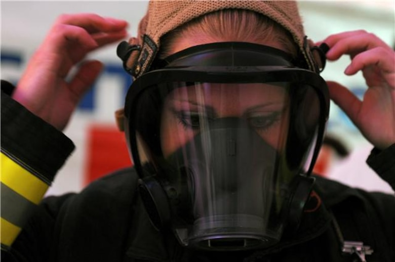Staff Sgt. Jessica Packard puts on her oxygen mask as she gets ready to compete in the individual relay event Nov. 19, 2009, at the Scott Firefighter Combat Challenge in Las Vegas. Sergeant Packard took 3rd place overall in the female individual competition. She is stationed at Goodfellow Air Force Base, Texas. (U.S. Air Force photo/Staff Sgt. Desiree N. Palacios)
