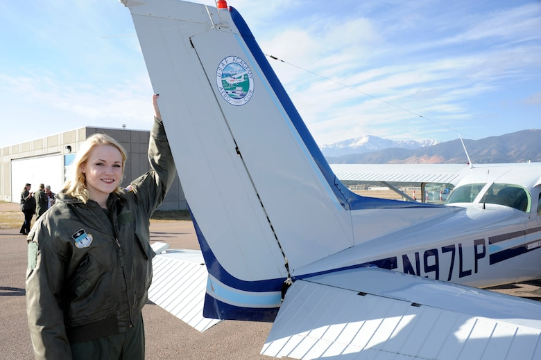 Hannah Marklin, 16, Academy's newest cadet for a day, poses at the tail of a Cessna during her visit to the Academy. Her weekend kicked off with a tour of the 98th Flying Training Squadron and a hanging harness training demo in its indoor training facility followed by an acrobatic glider demonstration and tour of the air traffic contol tower.