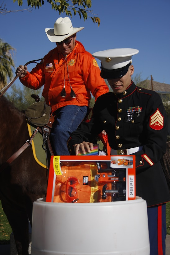Sgt. Jacobo Hernandez, a Marine volunteer with the Toys for Tots Foundation, puts toys in the donation barrel from the San Bernardino County Sheriff's Department Mounted Search and Rescue rider George Bowman at the base of the Combat Center's flag pole Nov. 22.