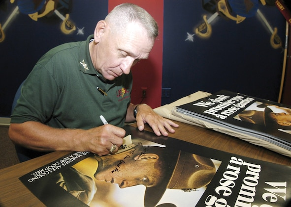 Charles Taliano signs one of his recruiting posters during a poster signing at Marine Corps Air Station Cherry Point, N.C., in 2003.