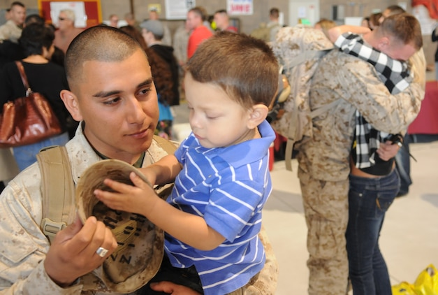 Lance Cpl. Ernest Carrillo, Marine Attack Squadron 214 ordnance technician, holds his son, Ernest Noel, for the first time in seven months after returning to the Marine Corps Air Station in Yuma, Ariz., Nov. 22, 2009, from a deployment to Afghanistan. Approximately 200 Marines from VMA-214 and Marine Aviation Logistics Squadron 13 arrived after spending half a year providing air support, armed reconnaissance and air defense for Marine Expeditionary Brigade-Afghanistan.