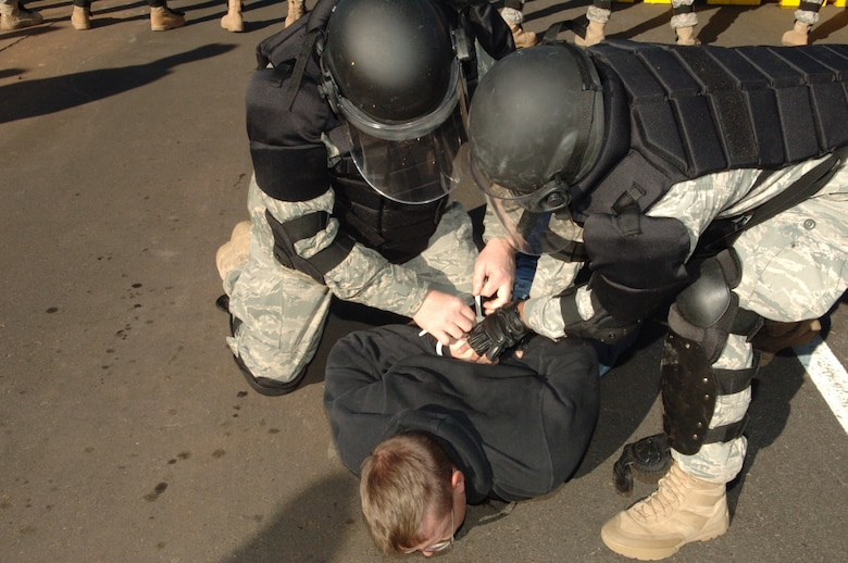 BUCKLEY AIR FORCE BASE, Colo. -- Members of the 460th Space Wing confrontation management team subdue a volunteer protestor Nov. 24. (U. S. Air Force photo by Tech. Sgt. Shirley Henderson)
