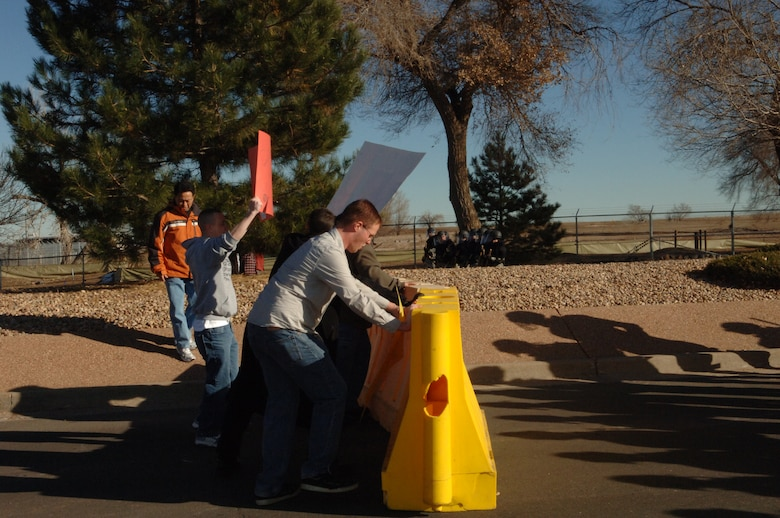 BUCKLEY AIR FORCE BASE, Colo. -- Volunteer mock protesters challenge barriers during an exercise Nov. 24. (U. S. Air Force photo by Tech. Sgt Shirley Henderson)
