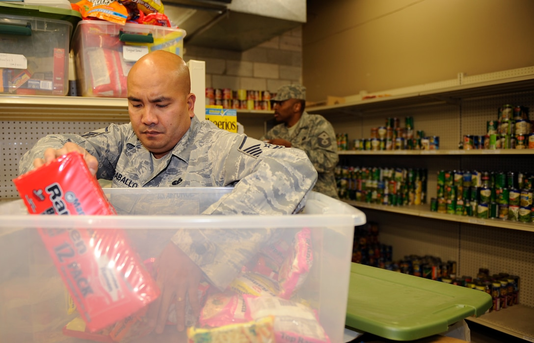 MOUNTAIN HOME AIR FORCE BASE, Idaho-- Master Sgt. David Caraballo, 366th Force Support Squadron Sustainment Services Flight superintendent, packs away food that was donated from the 366th Logistics Readiness Squadron's food drive. More than 5,200 pounds of food was donated recently to provide for families on base who are in need this holiday season. (U.S. Air Force photo by Airman 1st Class Renishia Richardson)