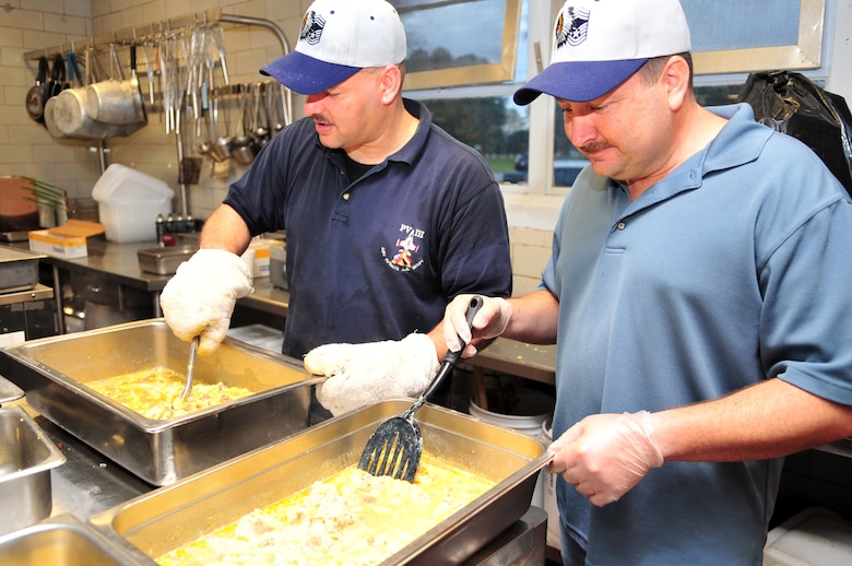 Chief Master Sgt. Dominick Tallarida, 911th Air Refueling Squadron chief, and Senior Master Sgt. Ken Jackson, 4th Equipment Maintenance Squadron munitions flight production section chief, scramble eggs during a Chief's Pancake Breakfast on Seymour Johnson Air Force Base, N.C., Nov. 20, 2009. Sergeant Jackson was recently selected for promotion to Chief Master Sergeant. During the breakfast base chiefs prepared food, served drinks and dished up food for Airmen passing through a buffet-style serving line. (U.S. Air Force photo/Airman 1st Class Rae Perry)