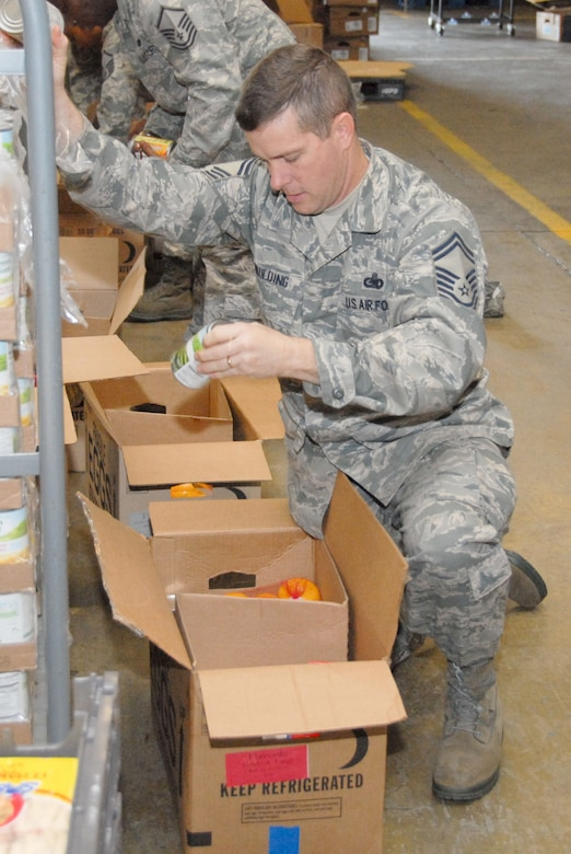 """Members of the Maxwell and Gunter Top 3 council """"share the joy"""" by putting together Thanksgiving boxes of food items for needy families. Above, Senior Master Sgt. Robert Spaulding of the Air Force Logistics Management Agency prepares a box that will go to a Maxwell-Gunter family identified by first sergeants that is in need. (U.S. Air Force photo/Bennett Rock)"""