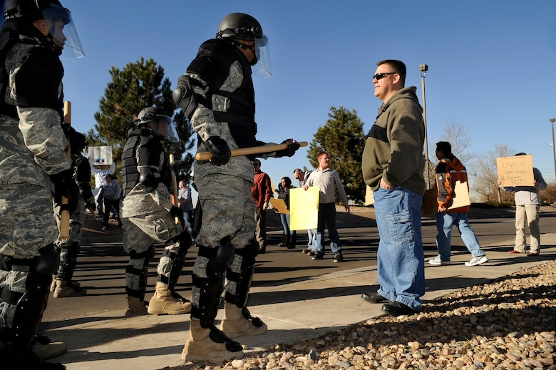 BUCKLEY AIR FORCE BASE, Colo. -- Members of the Buckley Air Force Base Confrontation Management Team make a barrier at the main gate during an exercise Nov. 24. (U.S. Air Force photo by Staff Sergeant Steve Czyz)