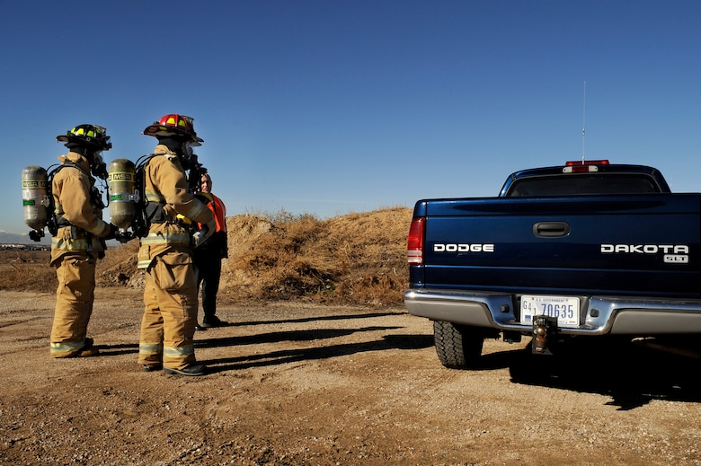 BUCKLEY AIR FORCE BASE, Colo. -- Buckley Firefighters plan their approach to enter a dangerous vehicle during an exercise Nov. 24. (U.S. Air Force photo by Staff Sergeant Steve Czyz)