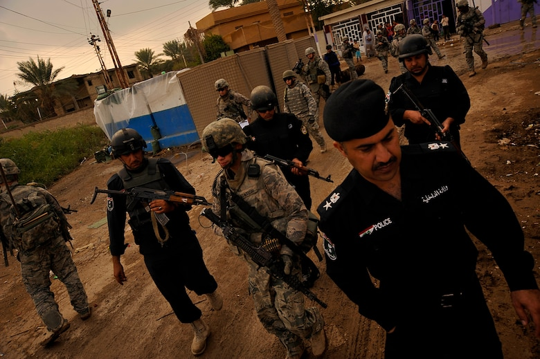 U.S. Air Force Airmen from the 732nd Expeditionary Security Forces Squadron Det. 2, deployed to Baghdad, Iraq, conduct a foot patrol through a Baghdad neighborhood, along with their counterparts from the Iraqi Police, in an effort to assess local checkpoints set up by the Iraqi Police, Nov. 19, 2009. (U.S. Air Force photo/Staff Sgt. Angelita Lawrence)