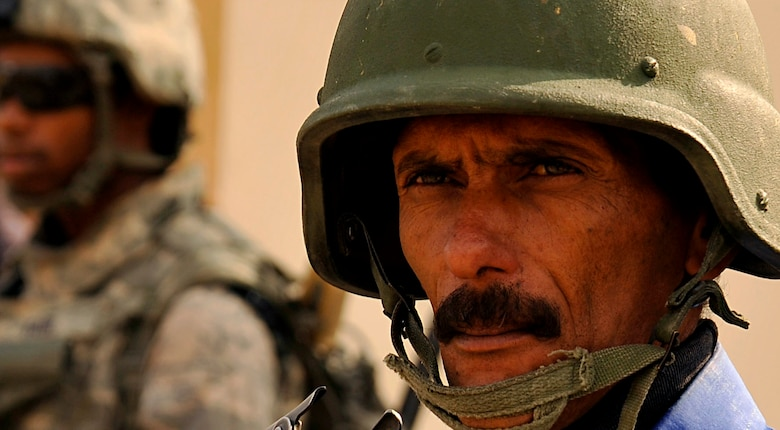 An Iraqi Police officer waits while Airmen from the 732nd Expeditionary Security Forces Squadron Det 2, deployed to Baghdad, Iraq, form up in order to conduct a foot patrol, Nov. 19, 2009. (U.S. Air Force photo/Staff Sgt. Angelita Lawrence)