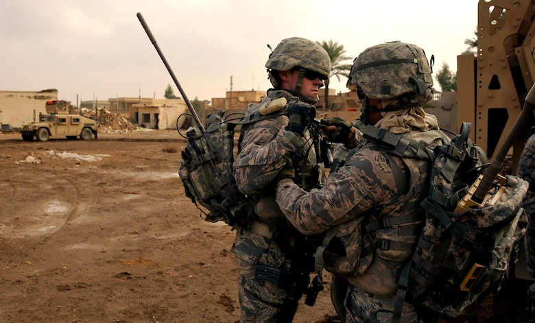 Richard Acosta and Joseph Hovis help one another with their gear prior to conducting a foot patrol through Baghdad with Iraqi Police. Both are senior airmen assigned to the 732nd Expeditionary Security Forces Squadron Det. 2, deployed to Baghdad. (U.S. Air Force photo/Staff Sgt. Angelita Lawrence)