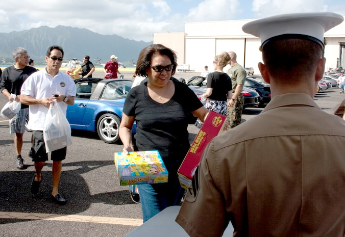 Members of the Oahu Porsche car owners club drop off donations of new, unwrapped toys with Marines during the 2009 Oahu Car Clubs Toys Cruise and Car Show at Marine Corps Base Hawaii Saturday, Nov. 28.  More than 500 cars representing more than 30 clubs participated, and more than 1,000 toys were donated to this year's collection effort.