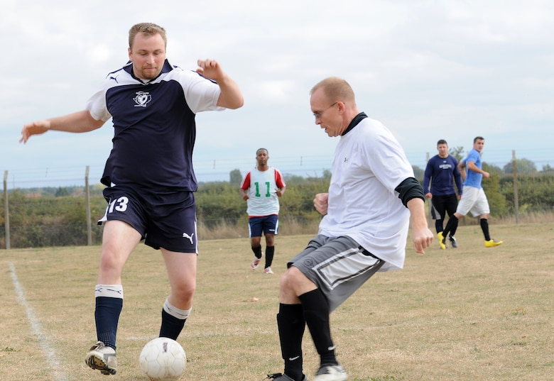 RAF MILDENHALL, England -- George Patsios, 488th Intelligence Squadron player (left), runs down the wing, dribbling past John Host, 100th Logistics Readiness Squadron player, in an intramural soccer match near the Hardstand Fitness Center here Sept. 30. The 100th LRS scored three points in a five-minute overtime session to take the match 6-3 against the combined 488th IS/95th Reconnaissance Squadron team. (U.S. Air Force photo/Senior Airman Thomas Trower)