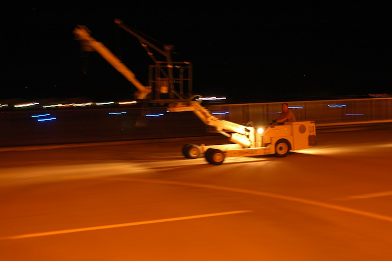 An F-16 crew chief drives specialized equipment on the 162nd Fighter Wing flightline at night on his way to remove conformal fuel tanks from an F-16 Desert Falcon. Guard maintainers work all hours to keep aircraft mission ready. (Air National Guard photo by Maj. Gabe Johnson)