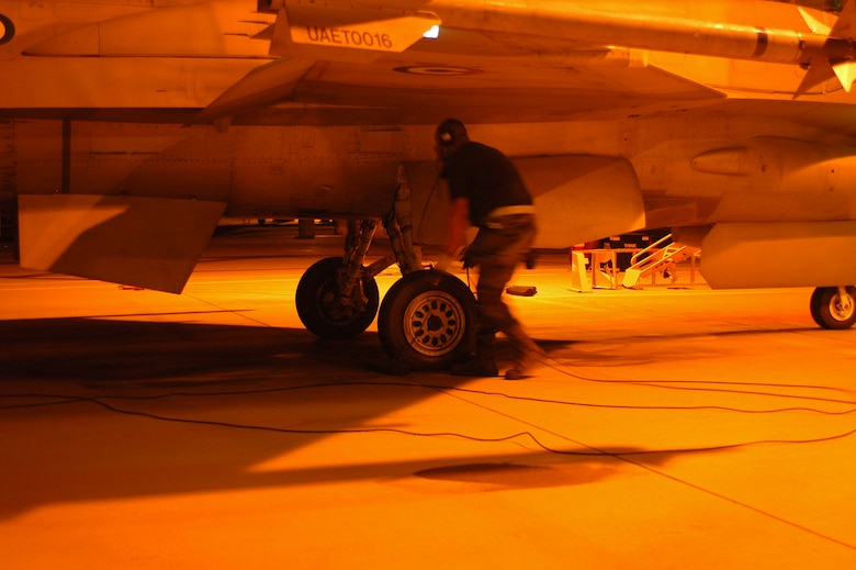 An F-16 crew chief prepares to pull chocks and launch his jet for a night mission. (Air National Guard photo by Maj. Gabe Johnson)
