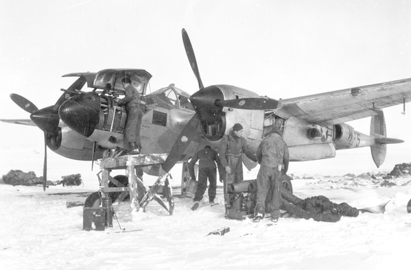 Rough field operations caused difficult working conditions for 9th Air Force maintenance personnel. Here a crew prepares to use an external heater to warm a P-38's frozen engine so it can be started while an armorer works on the guns in the nose while atop a makeshift stand. (U.S. Air Force photo)