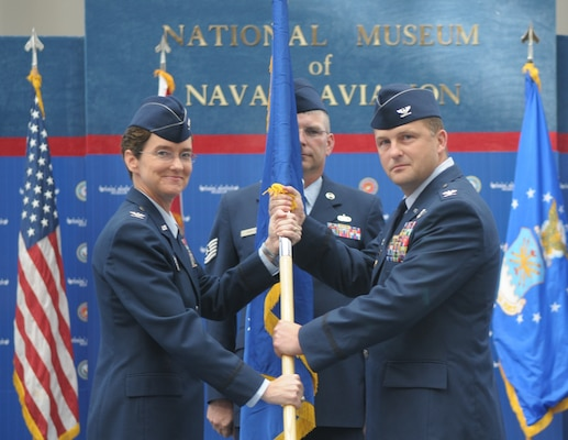 Col. Travis Willis accepts the unit flag to take command of the 479th Flying Training Group from Col. Jacqueline Van Ovost, commander of the 12th Flying Training Wing, Oct. 2 in the National Museum of Naval Aviation at Naval Air Station Pensacola, Fla. (U.S. Air Force photo by Joel Martinez)