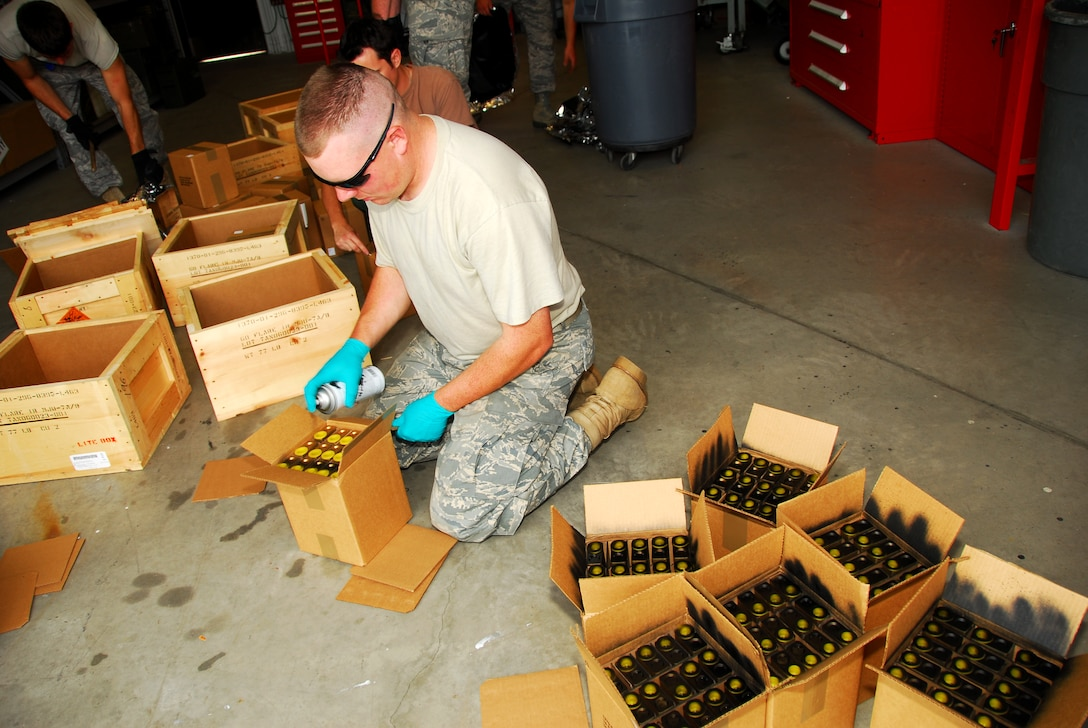 Munitions maintenance Senior Airman John Rench spray paints high intensity flares used on the F-16 Fighting Falcons.