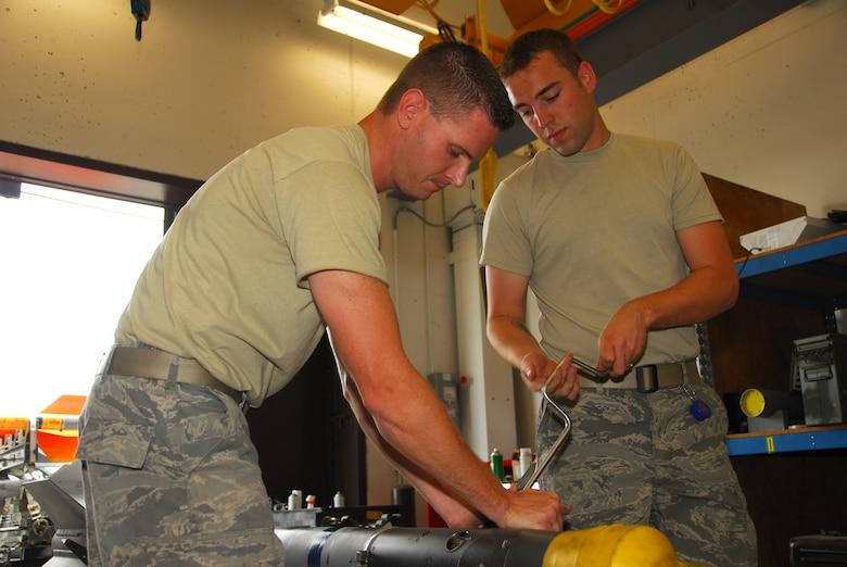 Munitions maitenance specialists Staff Sgt. Matt Hamilton (left) and Senior Airman James Jacobson assemble a AIM-9 Sidewinder missile.