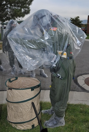 2nd Lt. Jason R Holbrook, 151st Operations Group, removes his chemical covering before moving to  a decontamination point during an Ability to Survive and Operate (ATSO) training exercise October 3. The exercise provided an opportunity for aircrew and support personnel to train in a simulated chemical environment. Air Force photo by Tech. Sgt. Michael D. Evans.