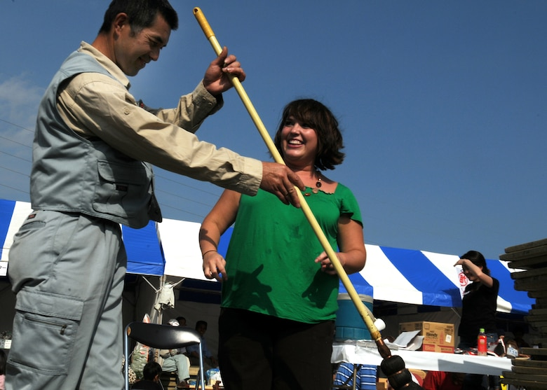 Mr. Masanori Kobashi shows Ms. Beth Gosselin, Chief of Public Affairs Operations at Kadena Air Base, Japan, how to paint her name with a hitofudegaki (large paint brush) at a local farm festival during their visit to Hyakuri Air Base, Japan, Oct. 04. The squadron is participating in an Aviation Training Relocation exercise between the U.S. Air Force and the Japan Air Self Defense Force from Oct. 5-9, 2009.