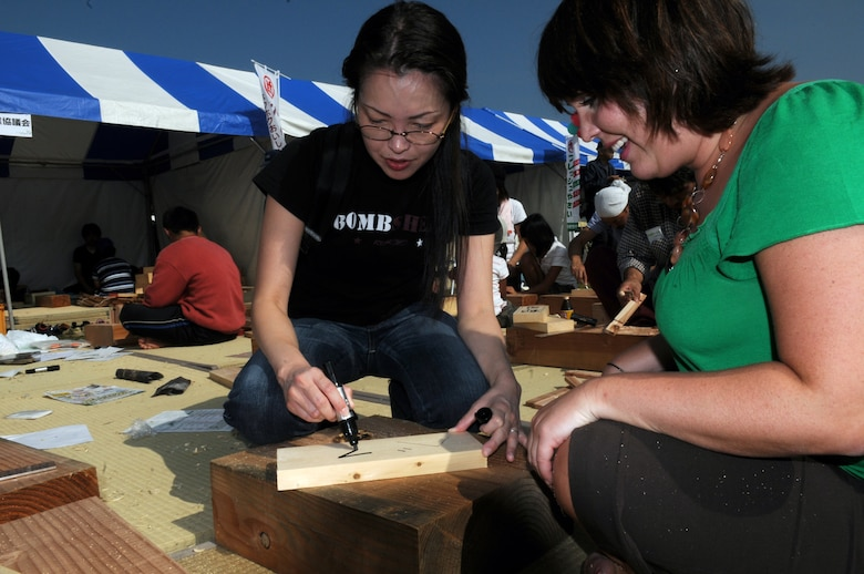 Mrs. Sayaka Higa, media relations specialist and Ms. Beth Gosselin, Chief of Public Affairs Operations, both at Kadena Air Base, Japan, try their wood-working skills at a local farm festival during their visit to Hyakuri Air Base, Japan, Oct. 04. The squadron is participating in an Aviation Training Relocation exercise between the U.S. Air Force and the Japan Air Self Defense Force from Oct. 5-9, 2009.