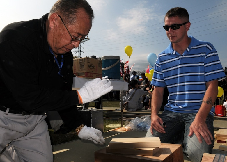 Mr. Masaichi Adachi, a wood-work master, shows Staff Sgt. James Bierman, from the 18th Equipment Maintenance Squadron at Kadena Air Base, Japan, tries his hand at Kibori (wood working) at a local farm festival during the visit to Hyakuri Air Base, Japan, Oct. 04. The squadron is participating in an Aviation Training Relocation exercise between the U.S. Air Force and the Japan Air Self Defense Force from Oct. 5-9, 2009.