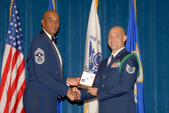 McGHEE TYSON AIR NATIONAL GUARD BASE, Tenn. -- Tech. Sgt. Tyler O. Weisgram, the unit deployment manager for the 49th Civil Engineer Squadron at Holloman AFB, N.M., receives the Distinguished Graduate Award for NCO Academy Class 09-6 at The Air National Guard Training and Education Center here from Chief Master Sgt. Leroy Frink, Sept. 30, 2009.  The Distinguished Graduate Award is presented to students in the top ten percent of the class.  It is based on objective and performance evaluations, demonstrated leadership, and performance as a team player.   (U.S. Air Force photo by Master Sgt. Kurt Skoglund)