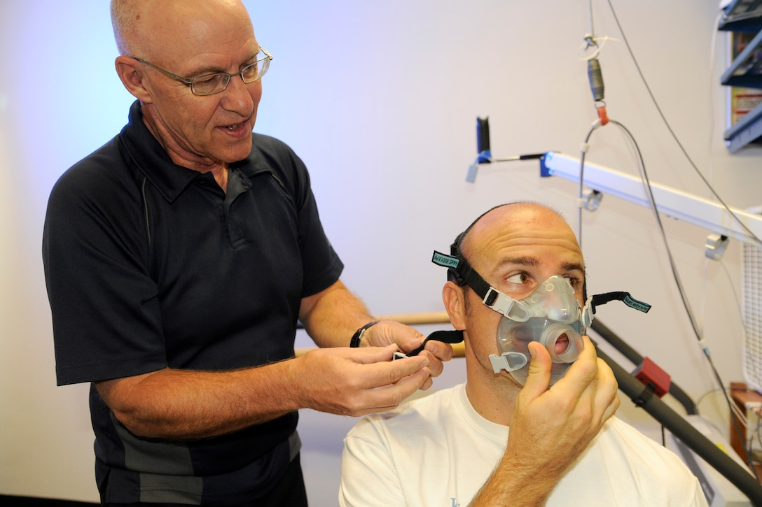 Jim LaChapelle helps Capt. Dustin Benker don an oxygen mask at the Air Force Academy's Human Performance Laboratory Sept. 29, 2009, in preparation for a test to check his oxygen consumption and carbon dioxide production while he works out. Captain Benker, a KC-135 pilot, is training for a marathon and triathlon. Mr. LaChapelle is an intern at the HPL. (U.S. Air Force photo/J. Rachel Spencer)
