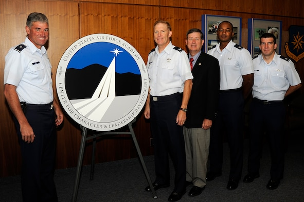 Brig. Gen. Samuel Cox and Col. John Norton unveil the Center for Character and Leadership Development's logo Sept. 28, 2009, at the U.S. Air Force Academy in Colorado Springs, Colo. General Cox is commandant of cadets at the Academy, and Colonel Norton is the CCLD director. Also pictured are retired Col. Tom Berry, deputy CCLD director; Lt. Col. Joe Sanders, assistant director for scholarship, and Lt. Col. Jim DeReus, assistant director for integration. The logo was designed by Chris Hureau of DenMar Services Inc. (U.S. Air Force photo/Rachel Boettcher)