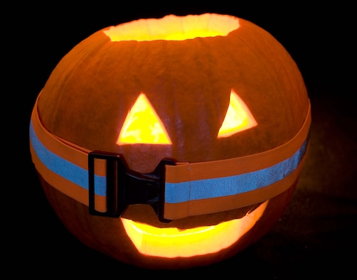 Freddy, 1st Fighter Wing Public Affairs' jack-o-lantern, dons a reflective belt in preparation for a safe Halloween. (U.S. Air Force photo/Staff Sgt. Barry Loo)