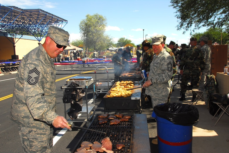 Chief Master Sgt. David Burton, left, turns a steak while Chief Master Sgt. George Silvas monitors chicken on the grill during the annual Steak Fry at the 162nd Fighter Wing, Oct. 4. (Air National Guard photo Master Sgt. Dave Neve)