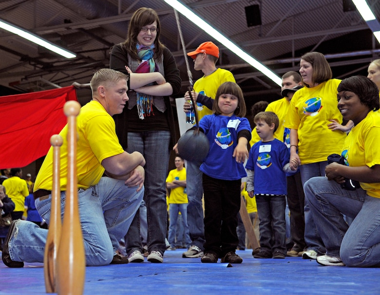 SPANGDAHLEM AIR BASE, Germany – Jennifer Erschfeld throws a tethered ball at bowling pins whiles volunteers cheer her on Oct. 8. Jennifer was one of about 100 children with special needs from Bitburg's St. Martin's School and Department of Defense Dependants Schools-Europe to attend the Special Children's Day held at the Skelton Memorial Fitness Center. The event required about 200 volunteers to help the children with games, lunch and an award ceremony at the end. (U.S. Air Force photo/Senior Airman Benjamin Wilson)