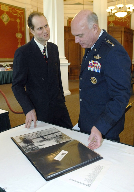 "Gen. Carrol H. ""Howie"" Chandler discusses Air Force imagery with photographer Nicholas Price at the Library of Congress Oct. 6, 2009, in Washington, D.C. The event was the official ceremony welcoming the acquisition of 60 images from the 'Cleared Hot!' Fine Art Photography Collection of the Air Force by Nicholas Price to the library. General Chandler is the Air Force vice chief of staff. (U.S. Air Force photo/Master Sgt. Stan Parker)"