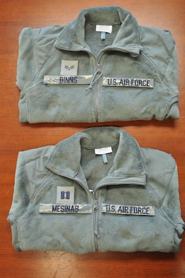 Pictured are sage green fleece outer garments with proper placement of name