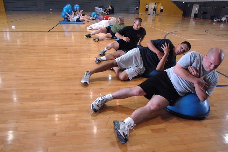 Members push through a set of side crunches during a hardcore class at the Southside Fitness Center, Ramstein Air Base, Germany, Oct. 7, 2009. The Southside and Northside Fitness Centers here offer hardcore classes Mondays through Fridays at noon and give members a thorough core muscle workout while preparing them for the physical training test. (U.S. Air Force photo by Tech. Sgt. Michael Voss)