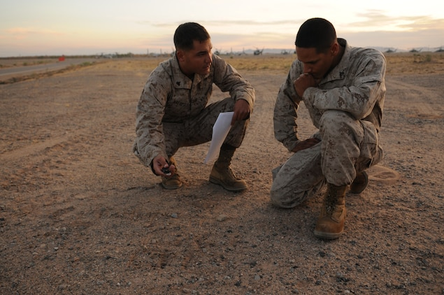 Cpl. Corey C. Haeuplte, squad leader with E Company, 2nd Battalion, 7th Marine Regiment, briefs one of his rifle team leaders Cpl. Joshua Diaz near the flight line at the Marine Corps Air Station in Yuma, Ariz., before a helicopter raid training exercise Oct. 10, 2009. Loading on to MV-22 Osprey aircraft in Yuma, the company's 1st Platoon flew to an urban training range in Twentynine Palms, Calif., in order to capture an insurgent leader, simulating a mission they could be called to perform during their next deployment. The battalion, based in Twentynine Palms, is scheduled to deploy with the 31st Marine Expeditionary Unit in early 2010, with E Company assigned to specialize in helicopter insertions and raids. Haeuplte, 23, is a native of Smyrna, Tenn., and Diaz, 21, is a native of Long Beach, Calif.