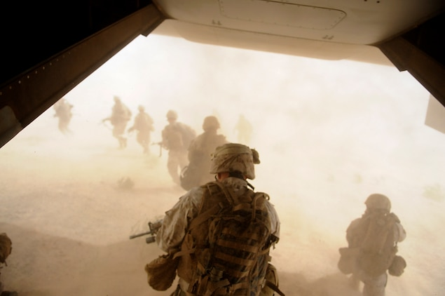Marines with E Company, 2nd Battalion, 7th Marine Regiment, storm from the back of an MV-22 Osprey into a disorienting cloud of sand kicked up by powerful rotor wash on the outskirts of an urban training range in Twentynine Palms, Calif., on Oct. 10, 2009. The battalion, based in Twentynine Palms, is scheduled to deploy with the 31st Marine Expeditionary Unit in early 2010, with E Company assigned to specialize in helicopter insertions and raids.