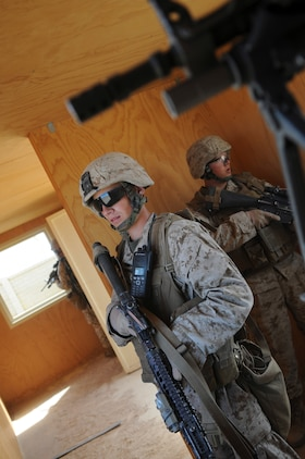 Lance Cpl. Michael R. Gravitt, rifle team leader, along with other members of with E Company, 2nd Battalion, 7th Marine Regiment, keep watch on the doors and windows of a building they just cleared in an urban training range in Twentynine Palms, Calif., on Oct. 10, 2009. The company's 1st Platoon flew from the Marine Corps Air Station in Yuma, Ariz, to Twentynine Palms, Calif., in order to raid a town and capture an insurgent leader, simulating a mission they could be called to perform during their next deployment. The battalion, based in Twentynine Palms, is scheduled to deploy with the 31st Marine Expeditionary Unit in early 2010, with E Company assigned to specialize in helicopter insertions and raids. Gravitt, 20, is a native of Moline, Ill.