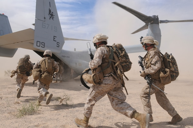 Members of E Company, 2nd Battalion, 7th Marine Regiment, run into the back of an MV-22 Osprey outside of an urban training range in Twentynine Palms, Calif., on Oct. 10, 2009. The company's 1st Platoon flew from the Marine Corps Air Station in Yuma, Ariz, to Twentynine Palms, Calif., in order to raid a town and capture an insurgent leader, simulating a mission they could be called to perform during their next deployment. The battalion, based in Twentynine Palms, is scheduled to deploy with the 31st Marine Expeditionary Unit in early 2010, with E Company assigned to specialize in helicopter insertions and raids.