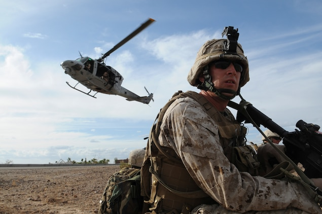 Lance Cpl. Mark W. Briggs, assaultman with E Company, 2nd Battalion, 7th Marine Regiment, waits to be extracted in UH-1 helicopters from an urban training range at the U.S. Army Yuma Proving Ground in Arizona during a helicopter raid exercise Oct. 12, 2009. Sixteen Marines landed on the outskirts of the range in four UH-1 helicopters and stormed the buildings from all sides searching for two insurgent leaders, simulating a mission they could be called to perform during their next deployment. The battalion, based in Twentynine Palms, Calif., is scheduled to deploy with the 31st Marine Expeditionary Unit in early 2010, with E Company assigned to specialize in helicopter insertions and raids. Briggs, 25, is a Salt Lake City native.