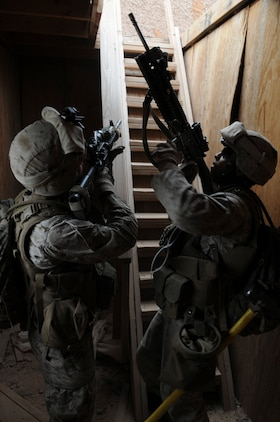 Cpl. Keith A. Nuckles, left, and Lance Cpl. Carlos Batista, with E Company, 2nd Battalion, 7th Marine Regiment, prepare to climb to the roof of a building to take out a mortar position in an urban training range at the U.S. Army Yuma Proving Ground in Arizona during a helicopter raid exercise Oct. 12, 2009. Sixteen Marines landed on the outskirts of the range in four UH-1 helicopters and stormed the buildings from all sides searching for two insurgent leaders, simulating a mission they could be called to perform during their next deployment. The battalion, based in Twentynine Palms, Calif., is scheduled to deploy with the 31st Marine Expeditionary Unit in early 2010, with E Company assigned to specialize in helicopter insertions and raids. Nuckles, 21, is a native of Pacoima, Calif., and Batista, 20, is a Miami-native.