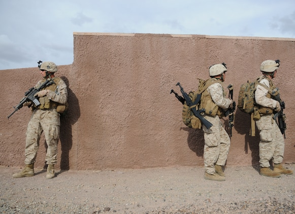 Lance Cpl. Mark W. Briggs, left, Lance Cpl. Tyson G. Bainum and Lance Cpl. Tyler Steffins with E Company, 2nd Battalion, 7th Marine Regiment, halt behind a wall moments before rushing to a landing site where they will be extracted in UH-1 helicopters from an urban training range at the U.S. Army Yuma Proving Ground in Arizona during a helicopter raid exercise Oct. 12, 2009. Sixteen Marines landed on the outskirts of the range in four UH-1 helicopters and stormed the buildings from all sides searching for two insurgent leaders, simulating a mission they could be called to perform during their next deployment. The battalion, based in Twentynine Palms, Calif., is scheduled to deploy with the 31st Marine Expeditionary Unit in early 2010, with E Company assigned to specialize in helicopter insertions and raids. Briggs, 25, is Salt Lake City-native, Bainum, 20, is a native of Canyon, Texas, and Steffins, 21, is from Marysville, Wash.