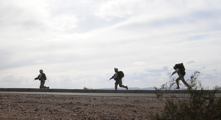 Members of E Company, 2nd Battalion, 7th Marine Regiment, run toward a landing site where they will be extracted in UH-1 helicopters from an urban training range at the U.S. Army Yuma Proving Ground in Arizona during a helicopter raid exercise Oct. 12, 2009. Sixteen Marines landed on the outskirts of the range in four UH-1 helicopters and stormed the buildings from all sides searching for two insurgent leaders, simulating a mission they could be called to perform during their next deployment. The battalion, based in Twentynine Palms, Calif., is scheduled to deploy with the 31st Marine Expeditionary Unit in early 2010, with E Company assigned to specialize in helicopter insertions and raids.
