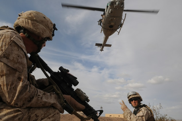 Sgt. Patrick R. Stephens, right, squad leader with E Company, 2nd Battalion, 7th Marine Regiment, signals Lance Cpl. Mark W. Briggs before extraction by in UH-1 helicopters from an urban training range at the U.S. Army Yuma Proving Ground in Arizona during a helicopter raid exercise Oct. 12, 2009. Sixteen Marines landed on the outskirts of the range in four UH-1 helicopters and stormed the buildings from all sides searching for two insurgent leaders, simulating a mission they could be called to perform during their next deployment. The battalion, based in Twentynine Palms, Calif., is scheduled to deploy with the 31st Marine Expeditionary Unit in early 2010, with E Company assigned to specialize in helicopter insertions and raids. Stephens, 25, is a native of Austin, Texas, and Briggs, 25, is a Salt Lake City native.
