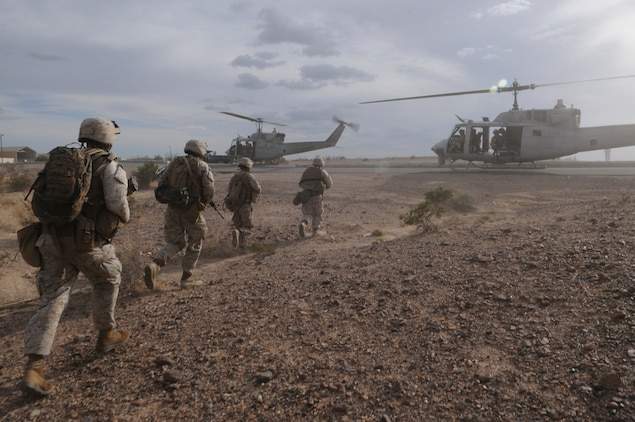 Members of E Company, 2nd Battalion, 7th Marine Regiment, move toward waiting UH-1 helicopters in order to be extracted from an urban training range at the U.S. Army Yuma Proving Ground in Arizona during a helicopter raid exercise Oct. 12, 2009. Sixteen Marines landed on the outskirts of the range in four UH-1 helicopters and stormed the buildings from all sides searching for two insurgent leaders, simulating a mission they could be called to perform during their next deployment. The battalion, based in Twentynine Palms, Calif., is scheduled to deploy with the 31st Marine Expeditionary Unit in early 2010, with E Company assigned to specialize in helicopter insertions and raids.