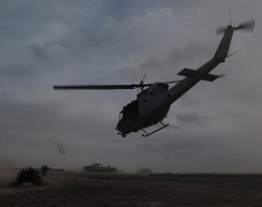 Two UH-1 helicopters carry members of E Company, 2nd Battalion, 7th Marine Regiment, from an urban training range at the U.S. Army Yuma Proving Ground in Arizona during a helicopter raid exercise Oct. 12, 2009. Sixteen Marines landed on the outskirts of the range in four UH-1 helicopters and stormed the buildings from all sides searching for two insurgent leaders, simulating a mission they could be called to perform during their next deployment. The battalion, based in Twentynine Palms, Calif., is scheduled to deploy with the 31st Marine Expeditionary Unit in early 2010, with E Company assigned to specialize in helicopter insertions and raids.